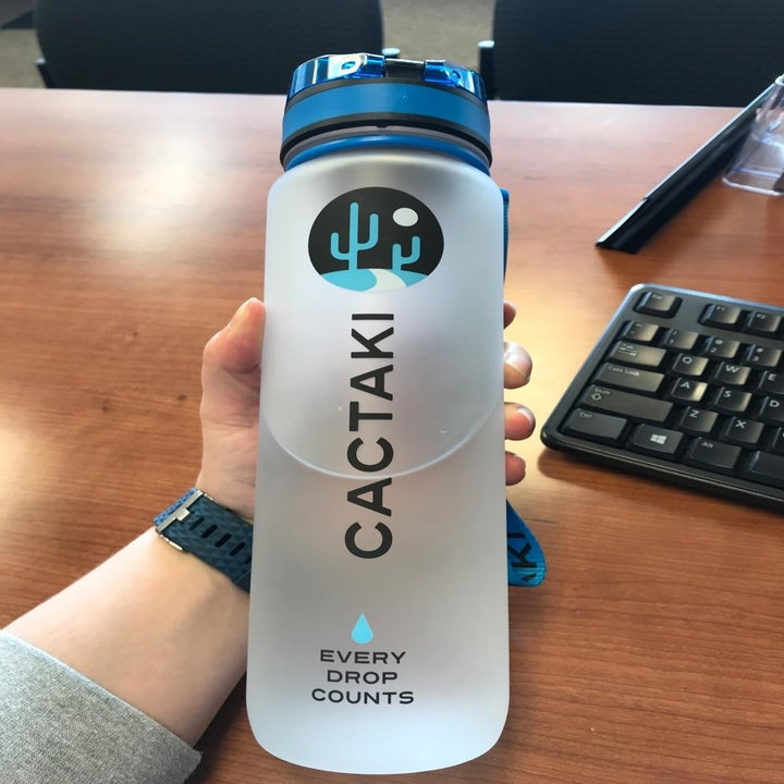 """A reviewer holding the water bottle at another angle to show the """"Cactaki"""" logo"""