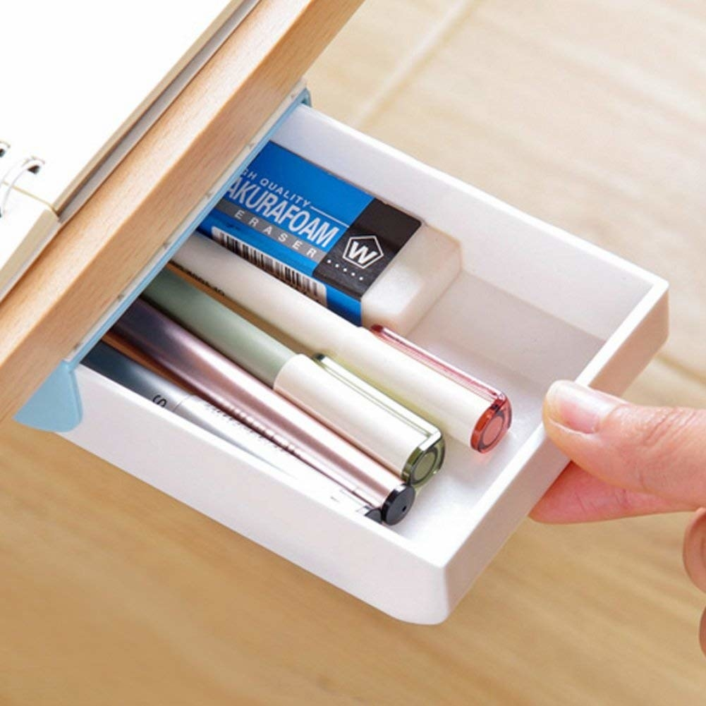 A small white drawer with pens in it installed in the underside of a desk