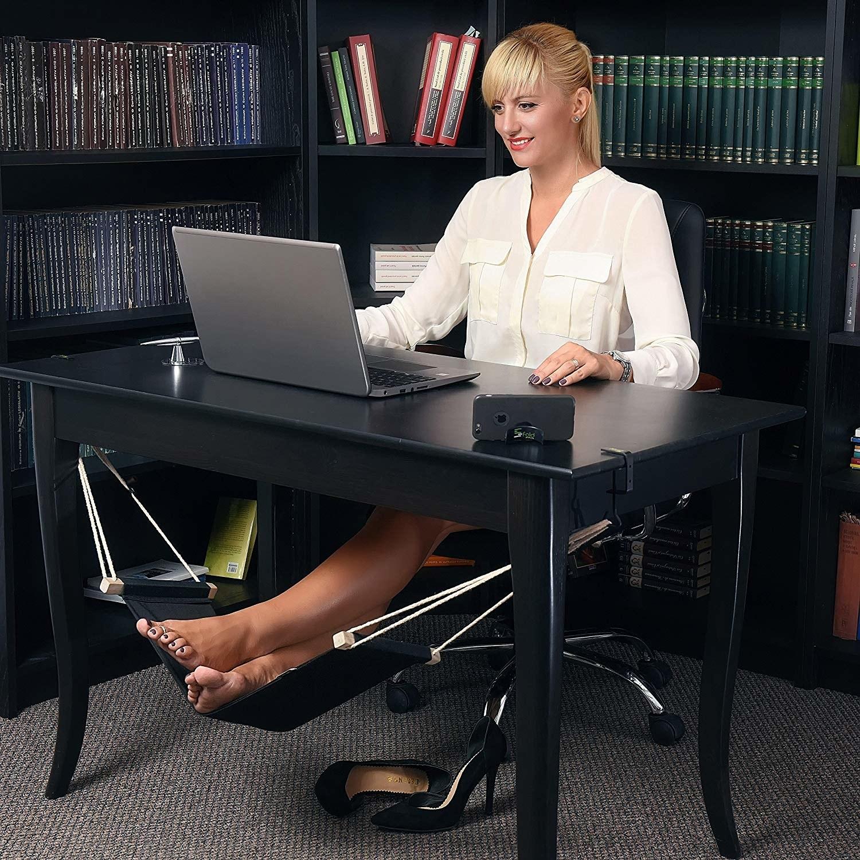 A model resting their feet in a hammock installed under their desk