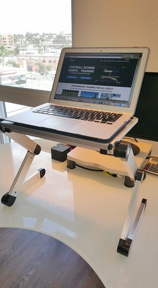 A silver adjustable standing desk propped on a table with a laptop on it