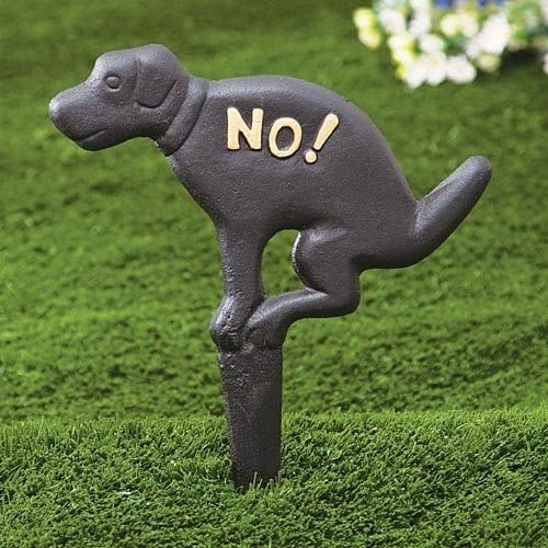 """Metal spike in grass of dog with word """"No!"""" to prevent dogs from using bathroom there"""