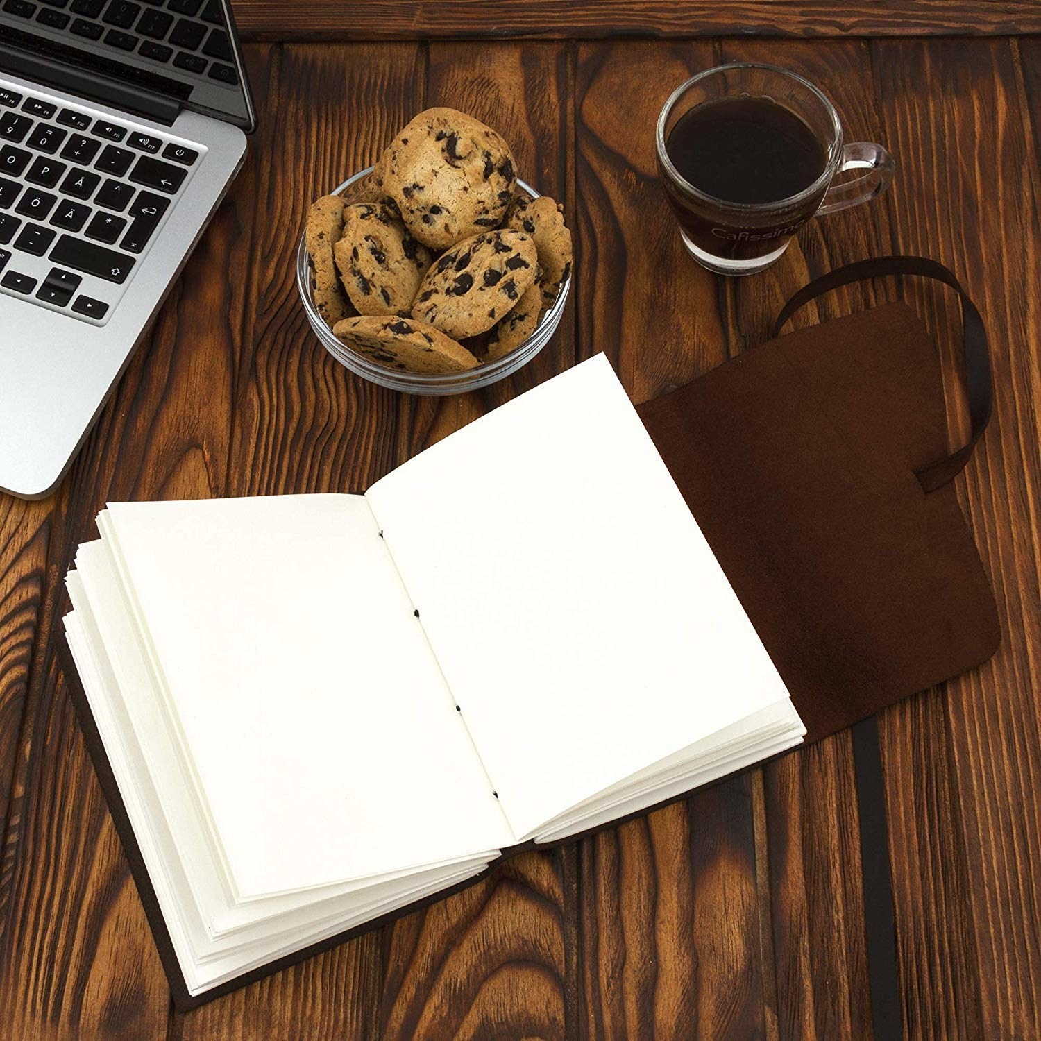 The journal kept on a table with a cup of coffee, bowl of cookie, and laptop.