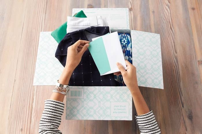 Hand opens styling card in Stitch Fix subscription box filled with clothes