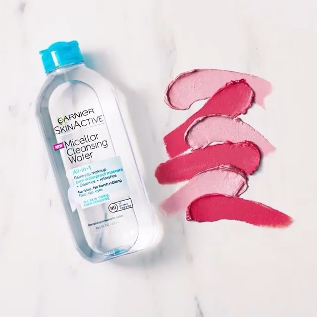 A bottle of the micellar water on a marble countertop next to several makeup smears