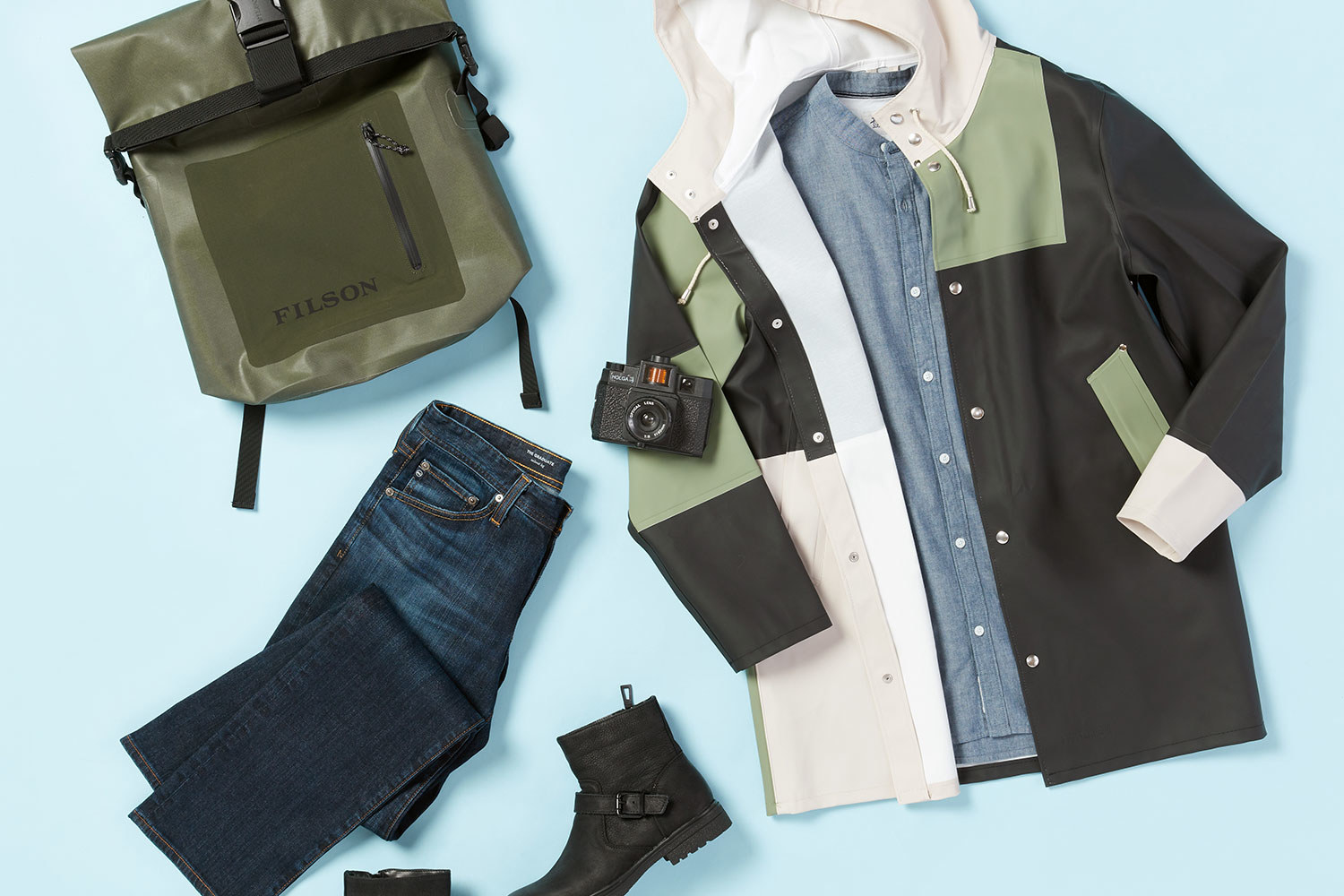 Trunk Club Box items including dark denim, a green, black, and white raincoat, and a green backpack