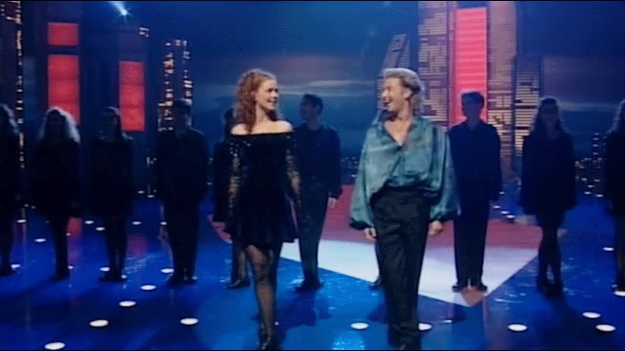 Michael Flatley in a blue shirt standing next to a dancer with a line of dancers behind them