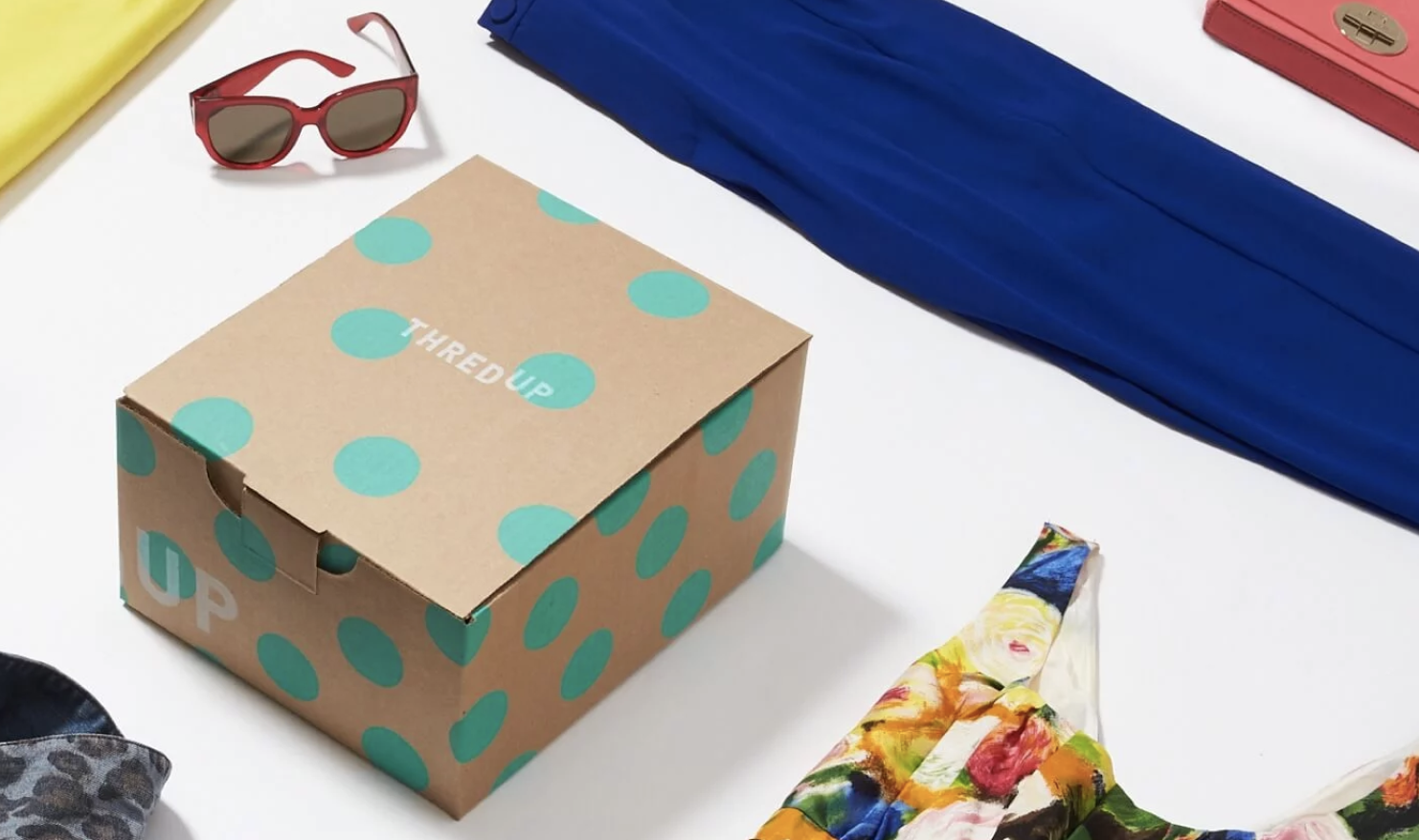 thredUP Goody Box filled with floral sleeveless top, navy blue pants, and dark red shades
