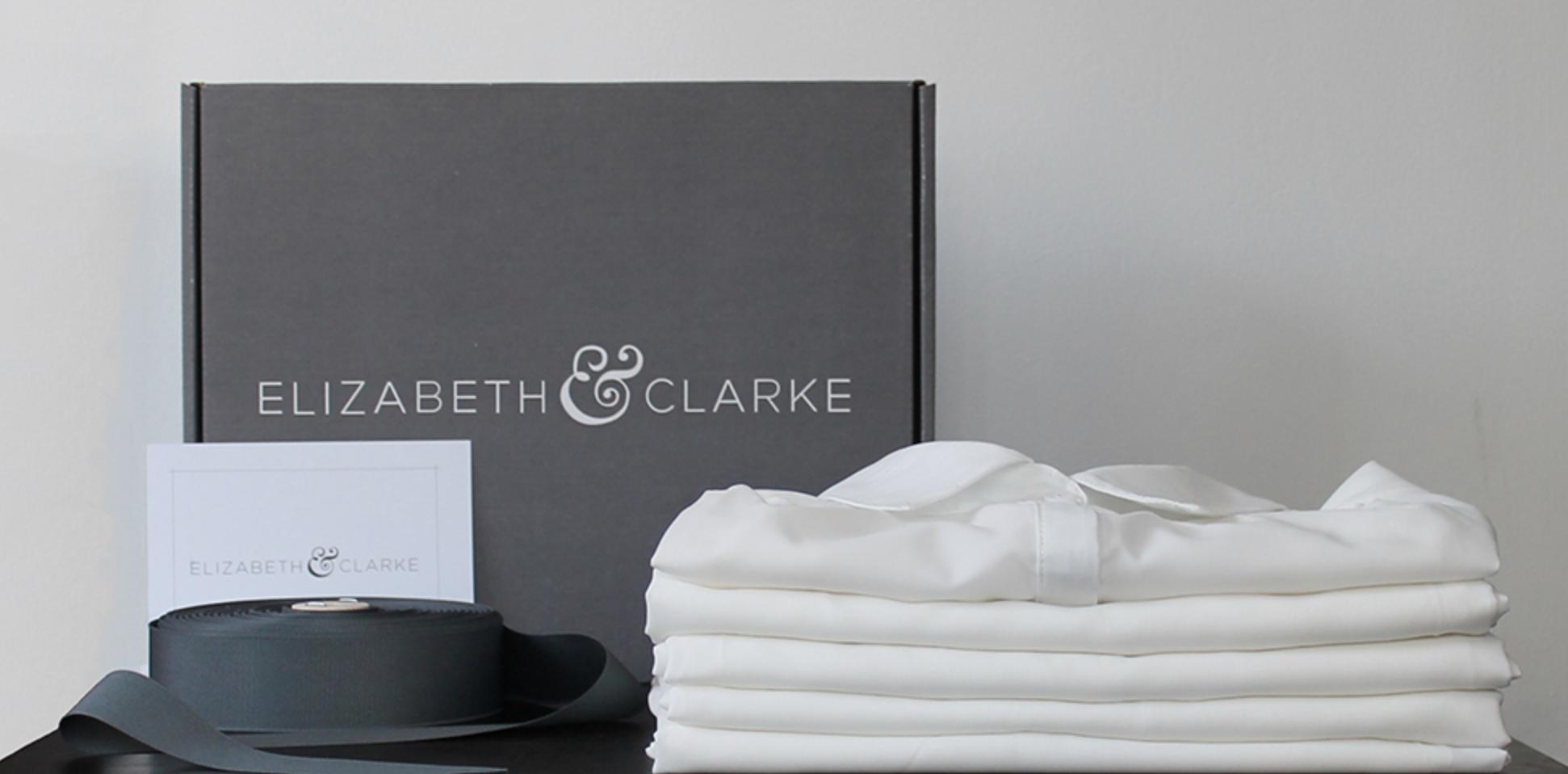Basic white button down shirts folded next to gray Elizabeth & Clarke box