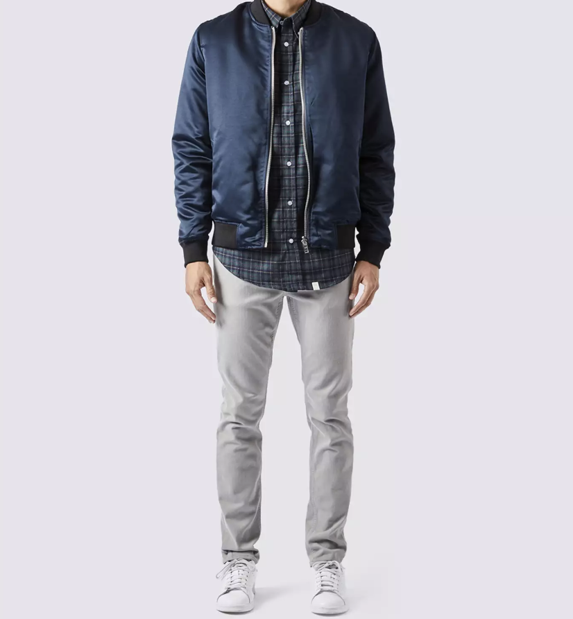 model in light gray jeans, white shoes, a blue flannel, and navy blue bomber jacket
