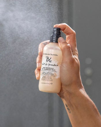 A hand spraying the dry shampoo mist