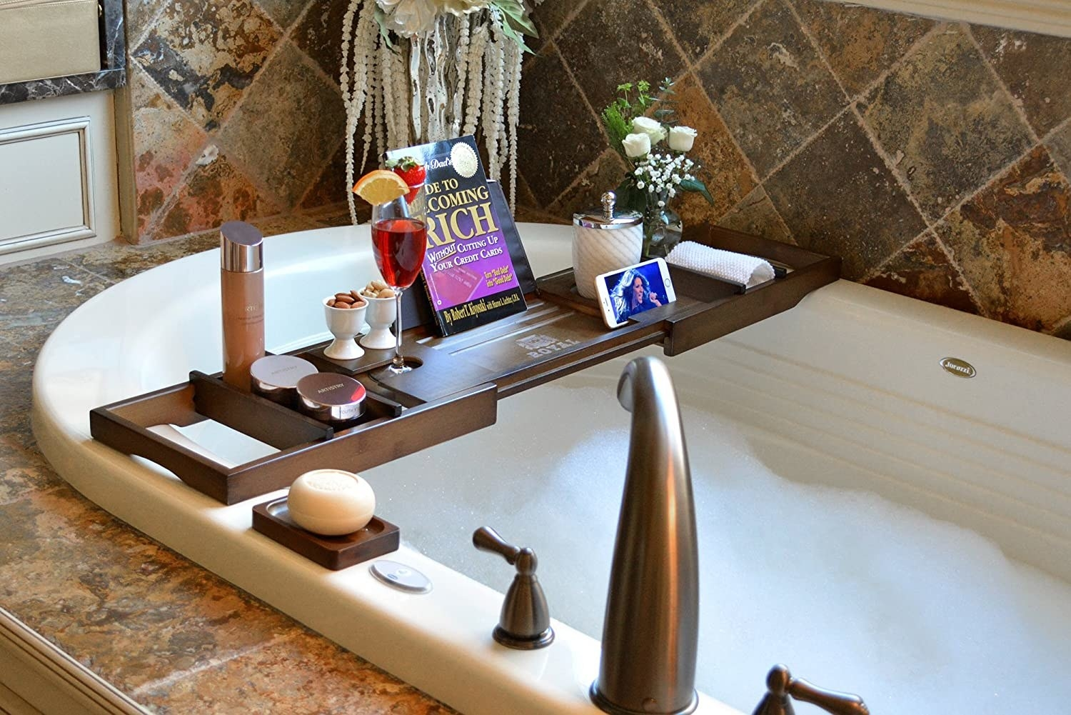 A bath caddy tray set up on a bath tub with various items like flowers, wine, mobile phone, etc. kept on it.