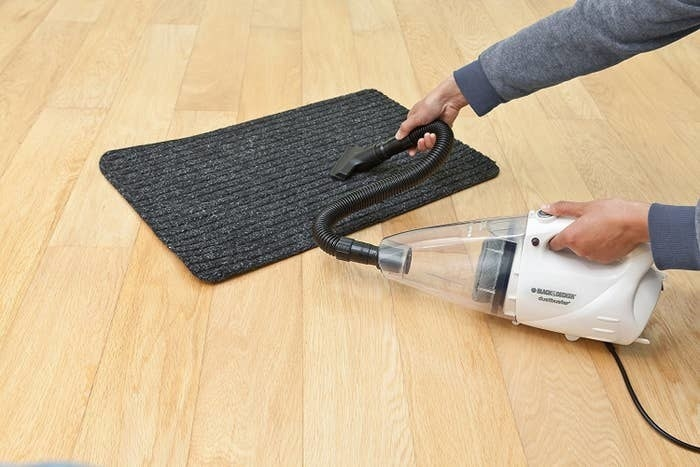 A person cleaning a grey mat with the vacuum cleaner.