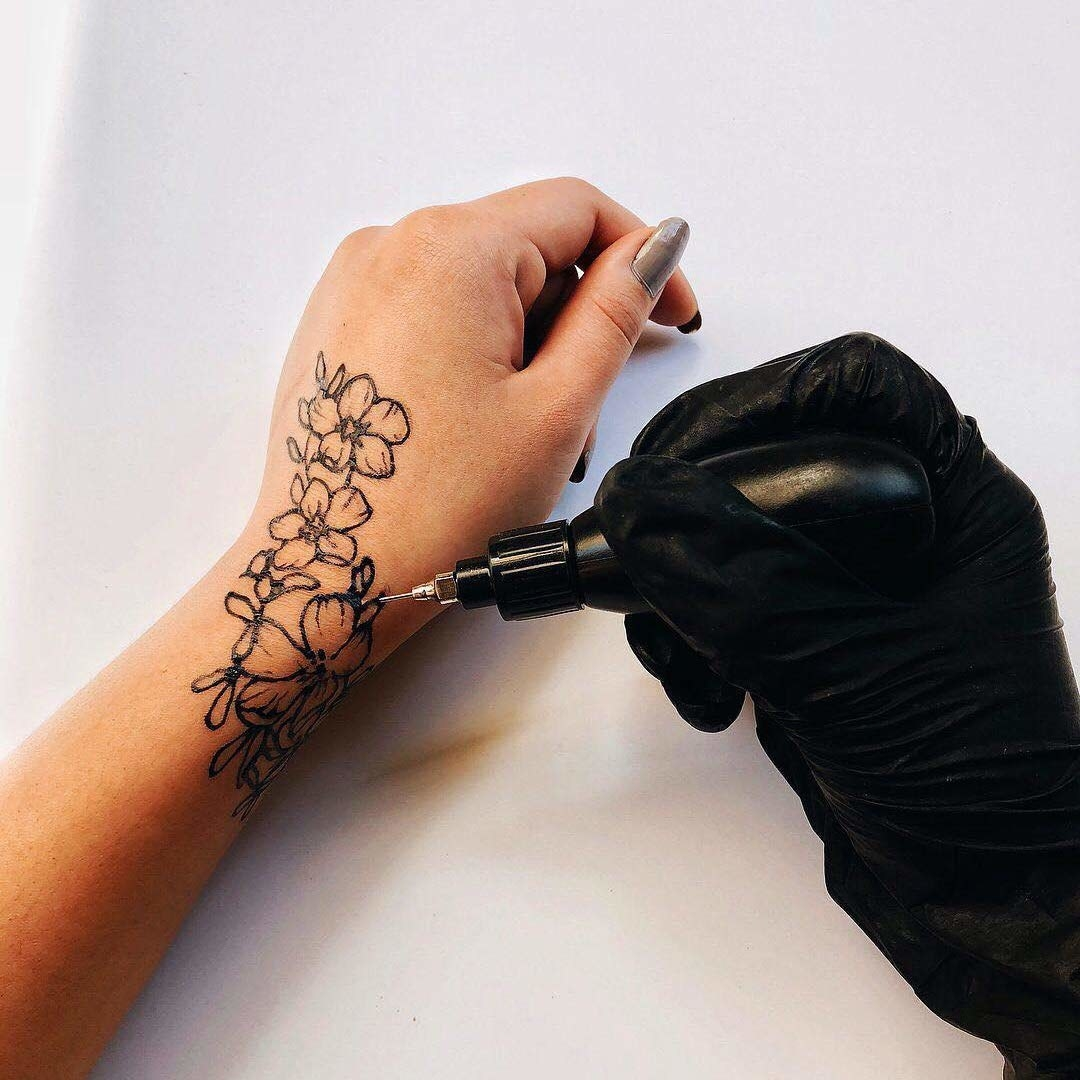 A person drawing a floral design on their hand