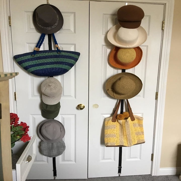 a different reviewer with the holder on the back of two closet doors and hats of all different types and purses hanging from it