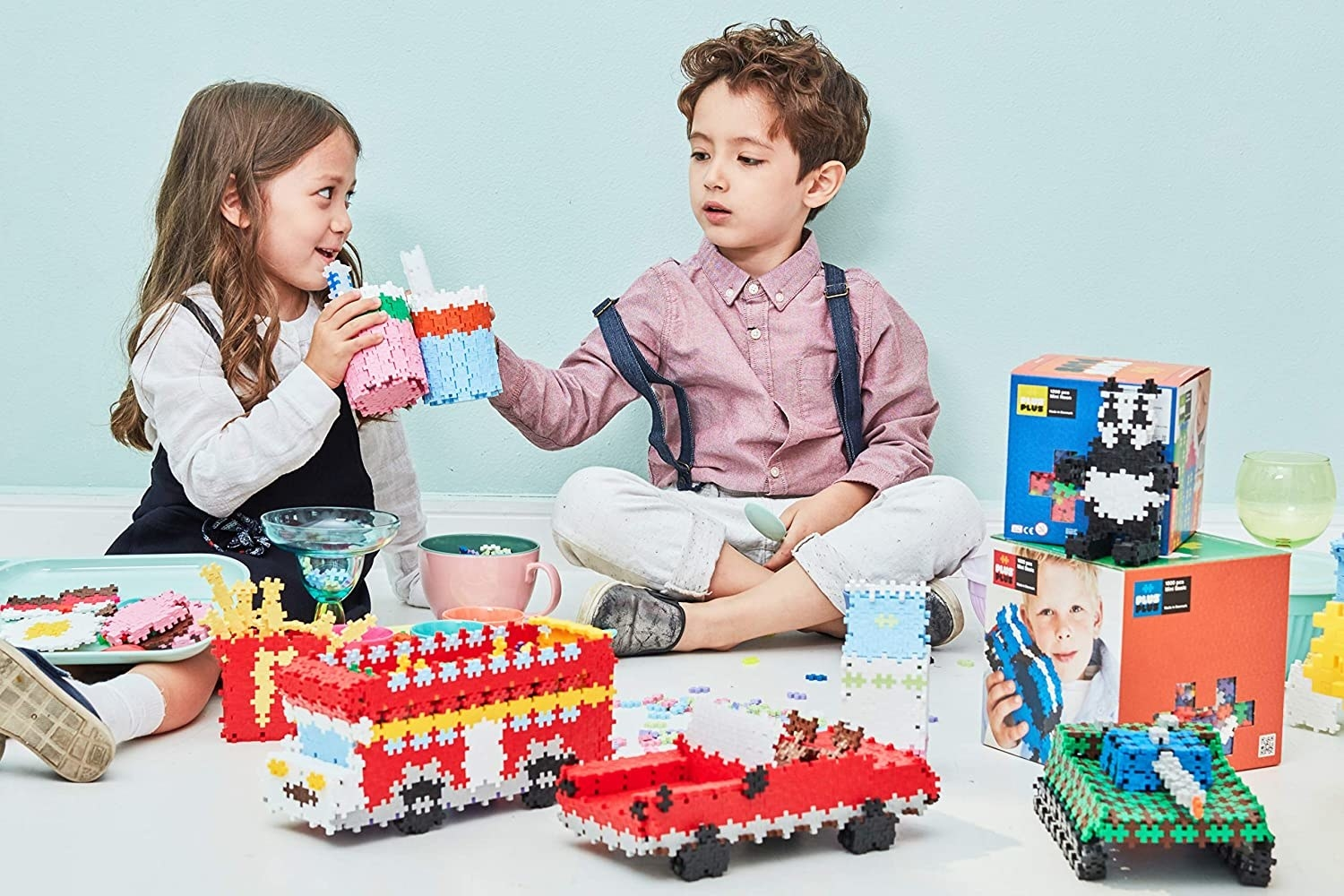 Two child models playing with vehicles and animals created with colorful puzzle blocks