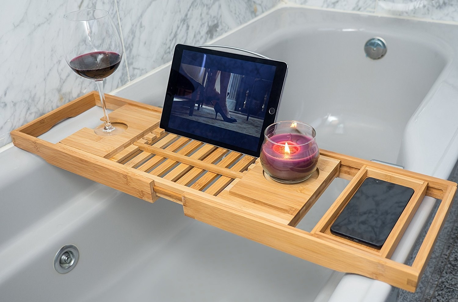 A bath caddy is stretched across a tub with a  glass of wine, a tablet and a candle
