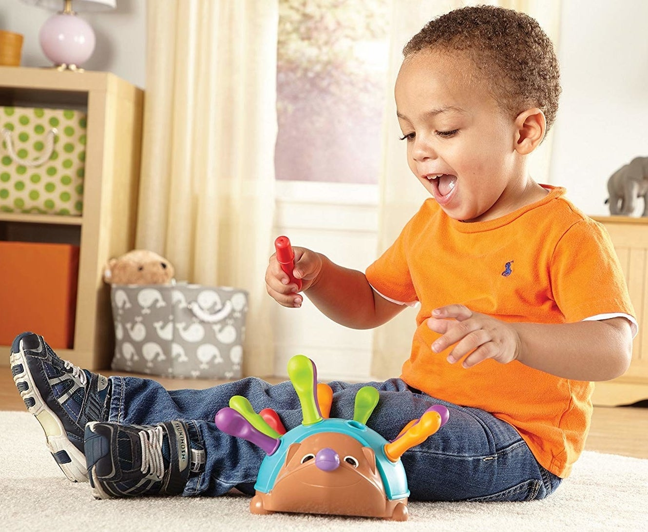 Child model playing with a colorful hedgehog toy