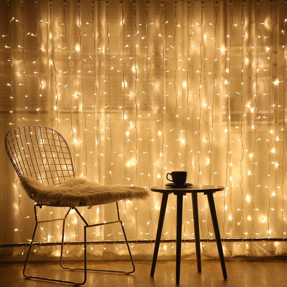 Twinkly lights on a wall beside a chair and a table