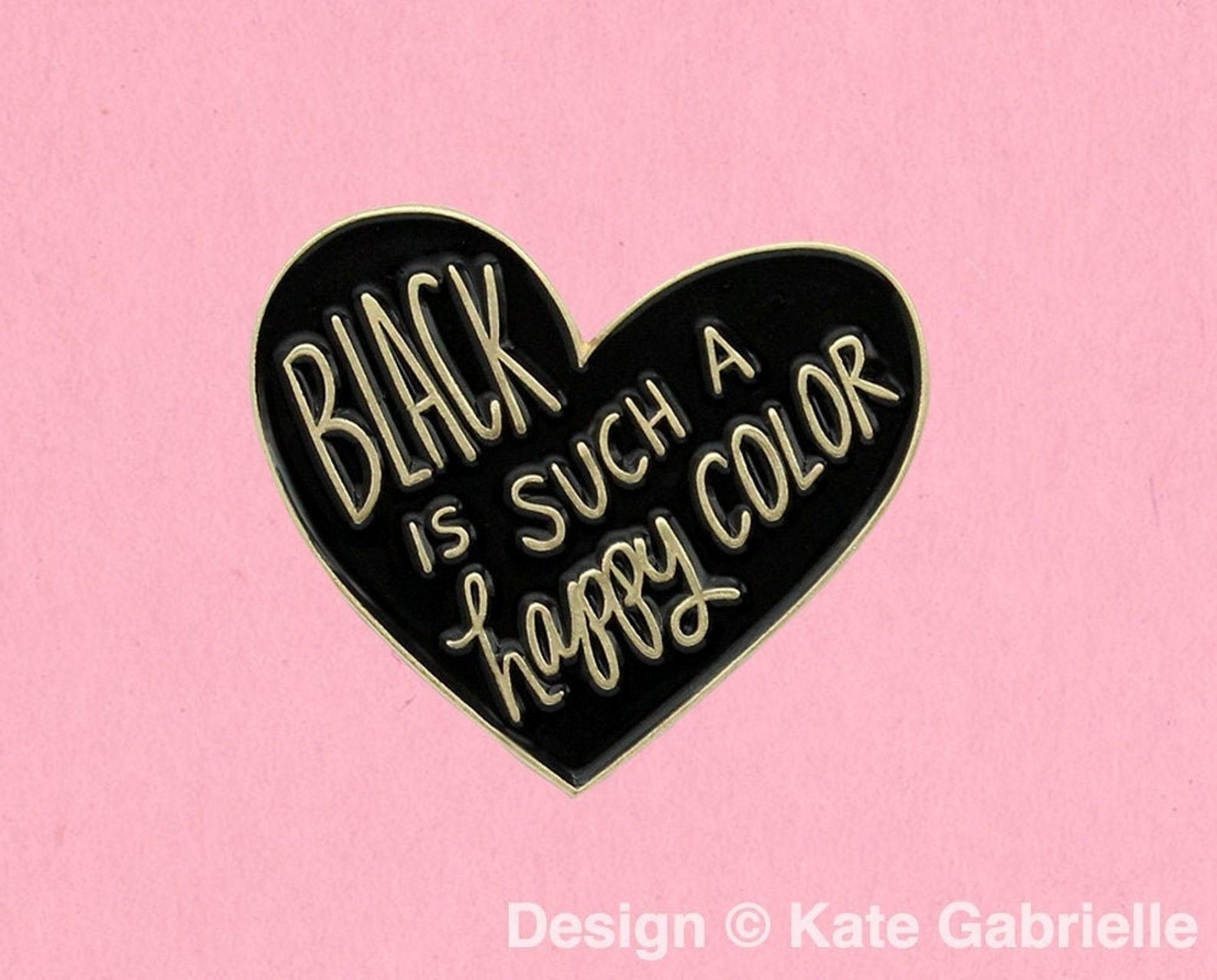 "a heart-shaped enamel pin that says ""black is such a happy color"" in gold font"