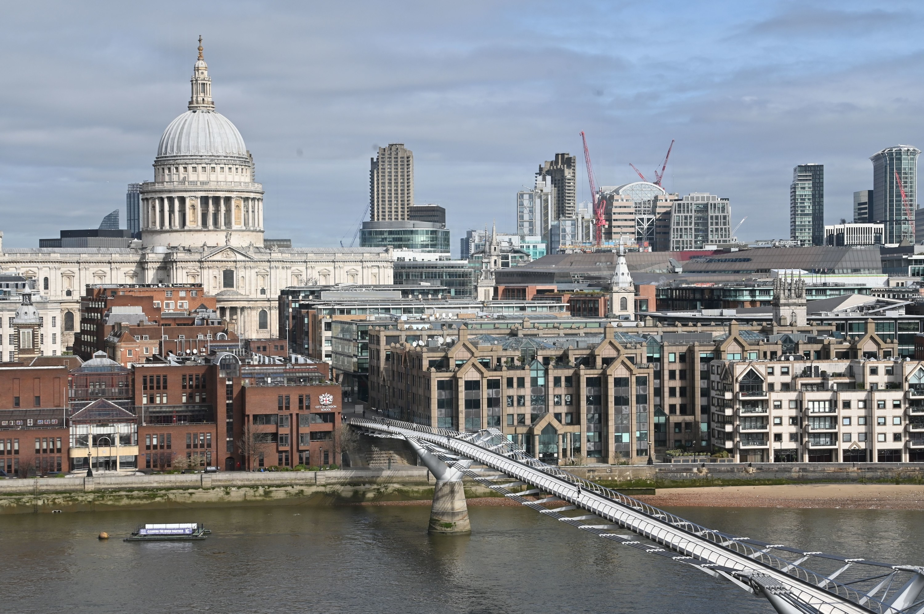 Pedestrians cross a quiet Millennium Footbridge across the River Thames in London in the mid-morning on March 17, 2020.