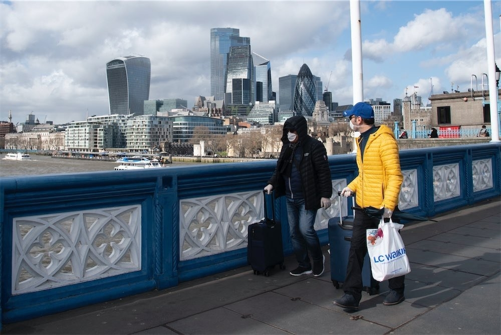 Tourists wear surgical masks on Tower Bridge on March 12.