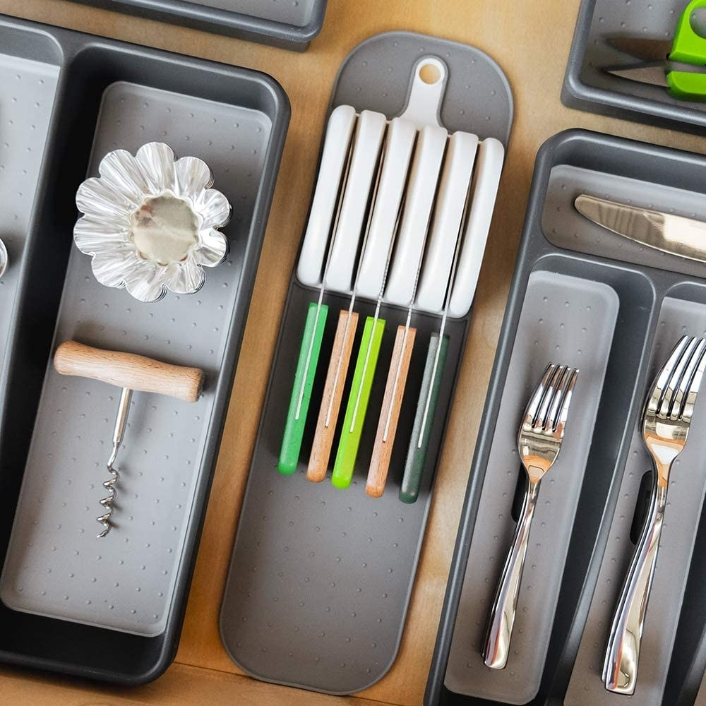 A knife mat inside a drawer next to cutlery and utensils