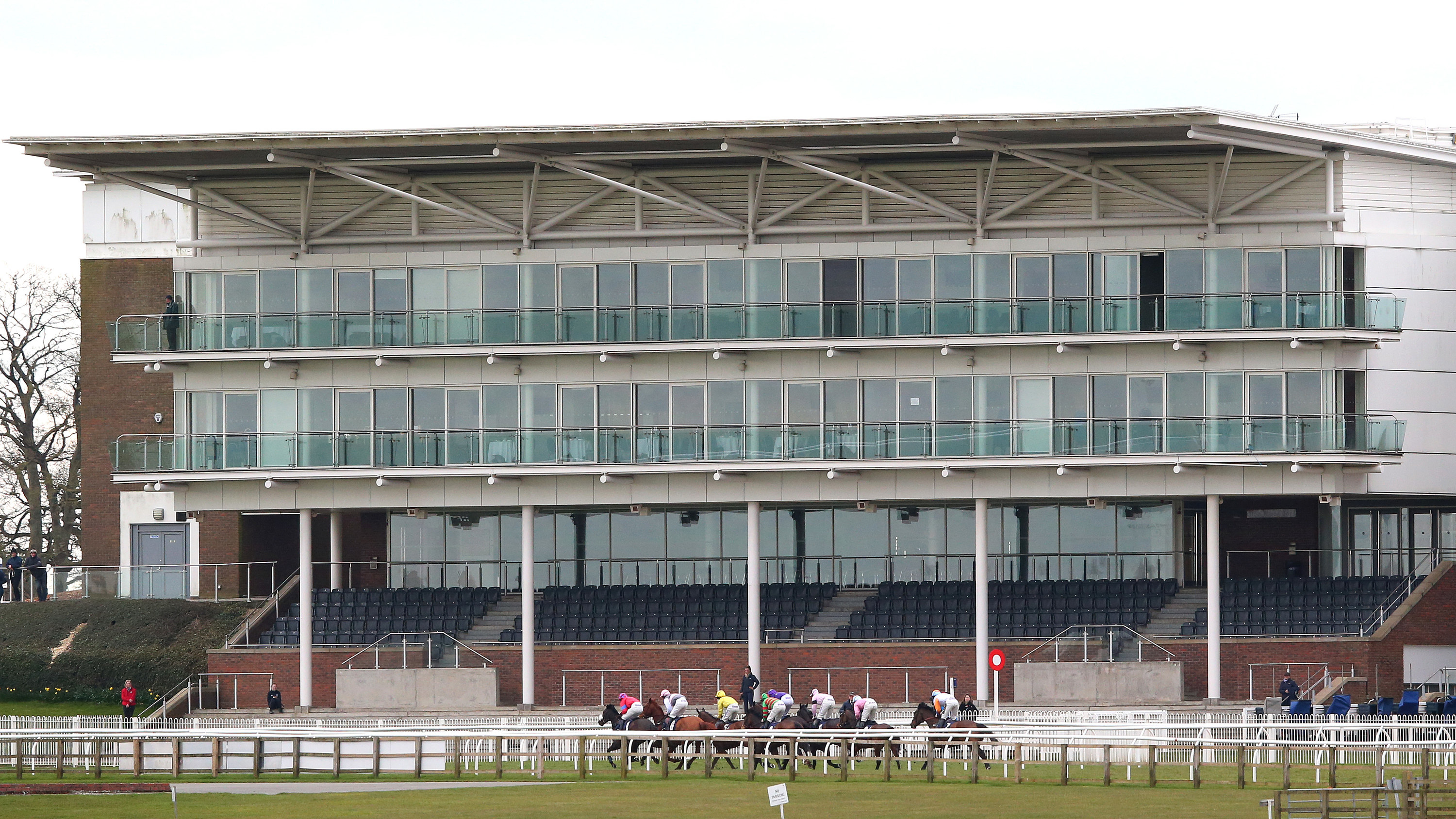 Empty stands are seen as horses and riders run past during a race