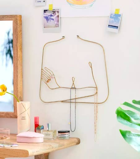 A female silhouette jewelry organizer with necklaces next to a dresser