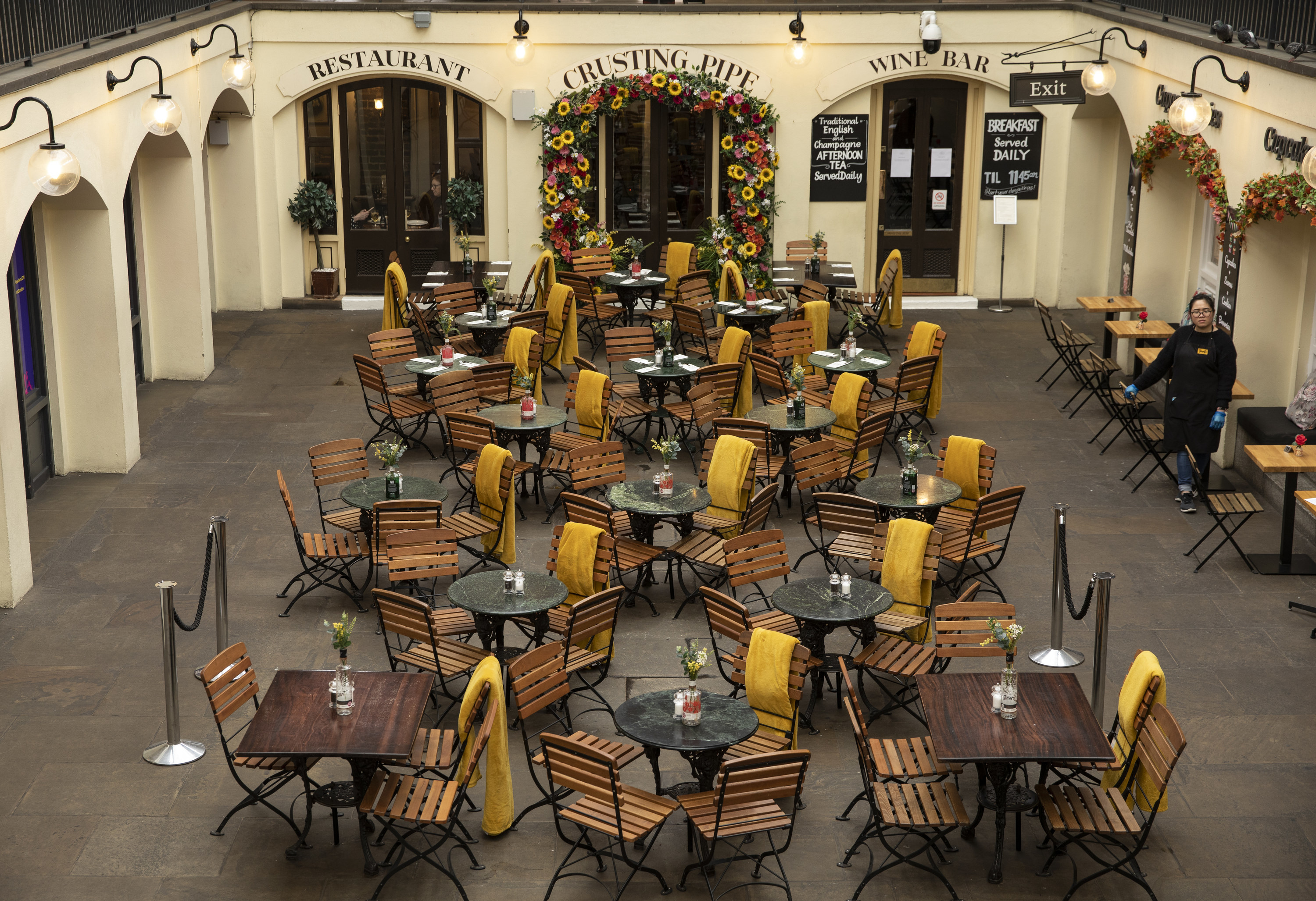 An employee waits over empty tables in Covent Garden on March 17, 2020
