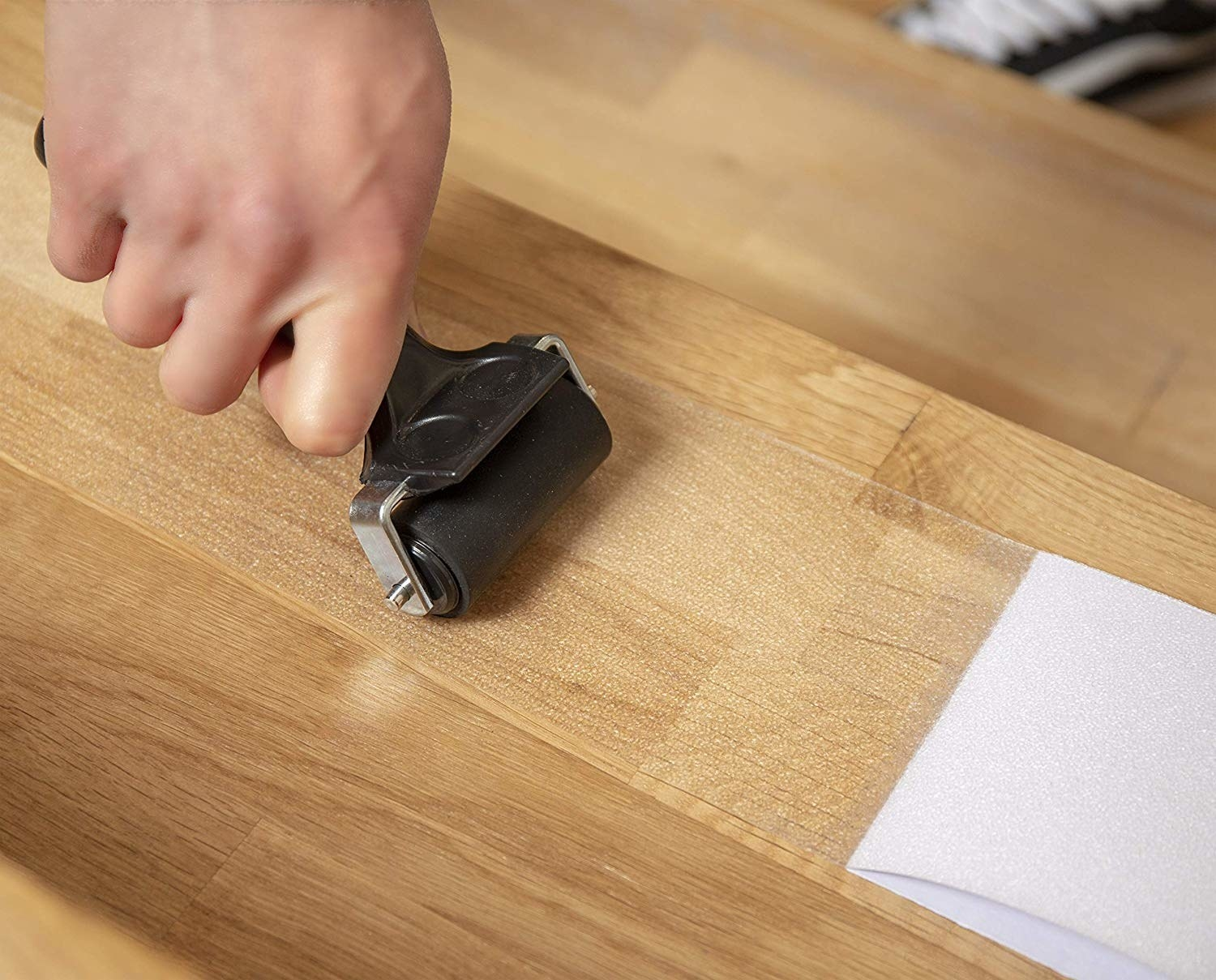 A hand rolls the transparent anti-slip tape across some wooden stairs