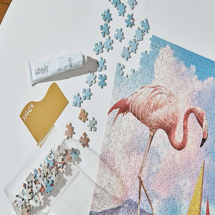 Flamingo puzzle in pieces with tube of glue beside it
