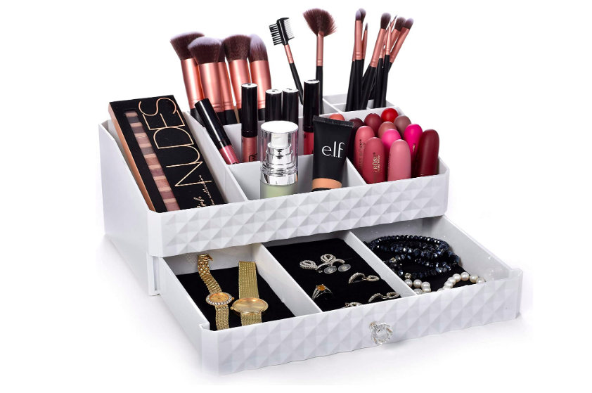 Cosmetic storage box filled with makeup brushes on top and jewelry on the bottom