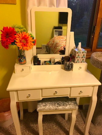 Reviewer's white vanity set with a bouquet of flowers and makeup compartments