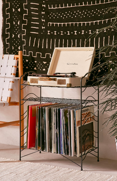 A black storage shelf with a record player on top and several vinyls on the bottom