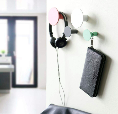 Pink, white, and green wall hooks holding headphones and a wristlet
