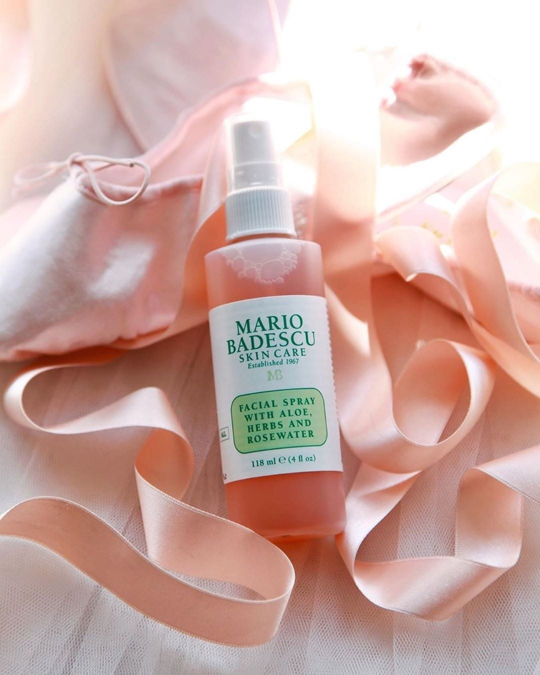A bottle of the facial spray rests on some tulle and ribbon