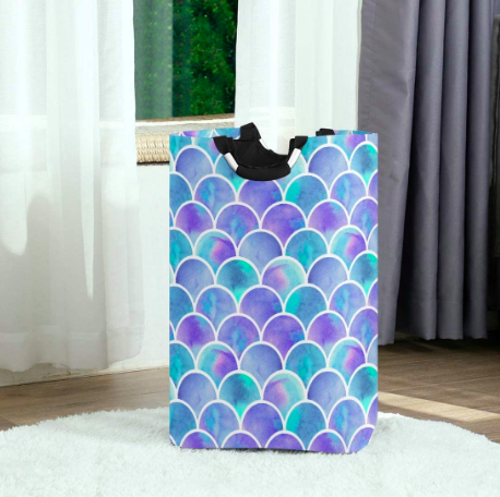 Purple and blue mermaid-pattern laundry basket on a white rug