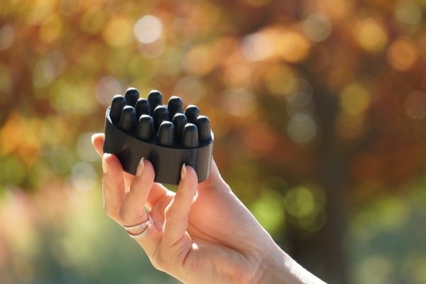 a hand holding a chunky bar of charcoal soap designed to massage the body
