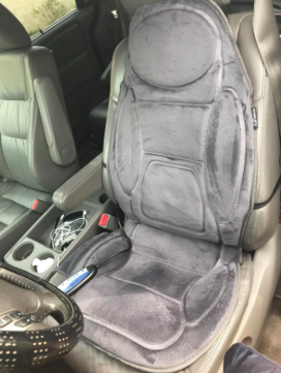 reviewer pic of gray soft massaging cushion on the seat and back of a car driver's seat