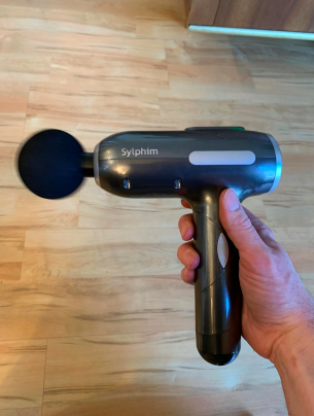 reviewer holding the massager that has a handle and body like a power drill with a massaging ball at the end