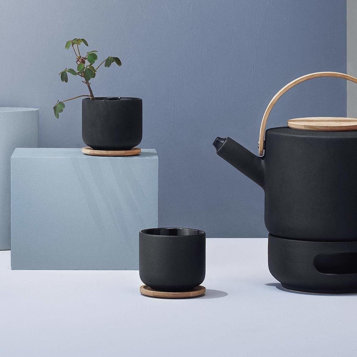 A minimal arrangement of the tea pot and two tea cups