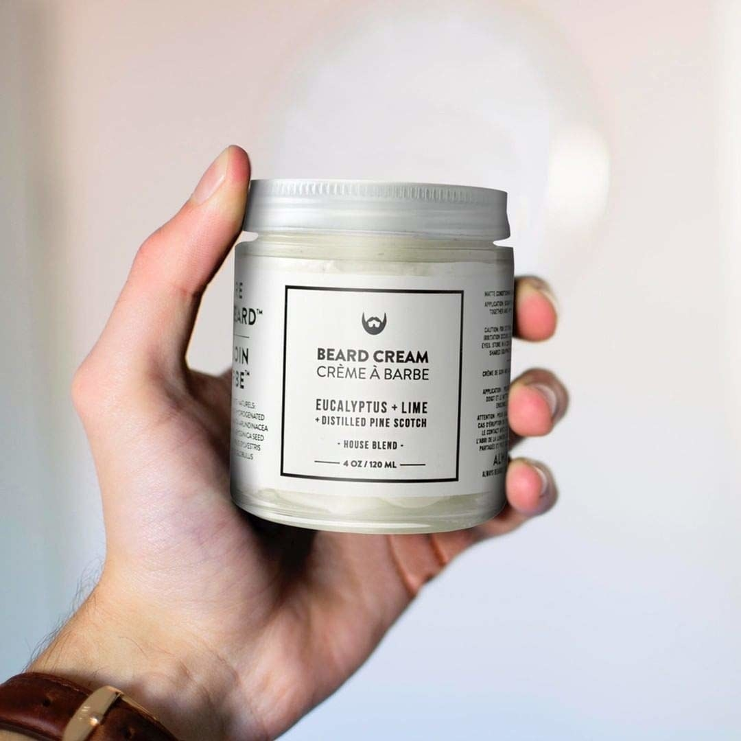 A hand holds up the jar of beard cream against a neutral background