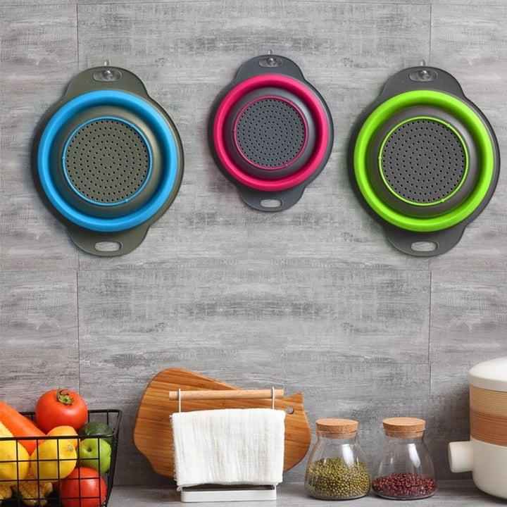 Set of three collapsible colanders hanging on wall