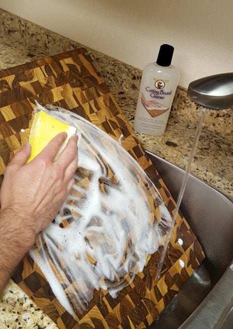 Reviewer cleaning cutting board with cleaner and sponge