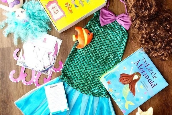 A mermaid children's book and costume laid out with other themed items