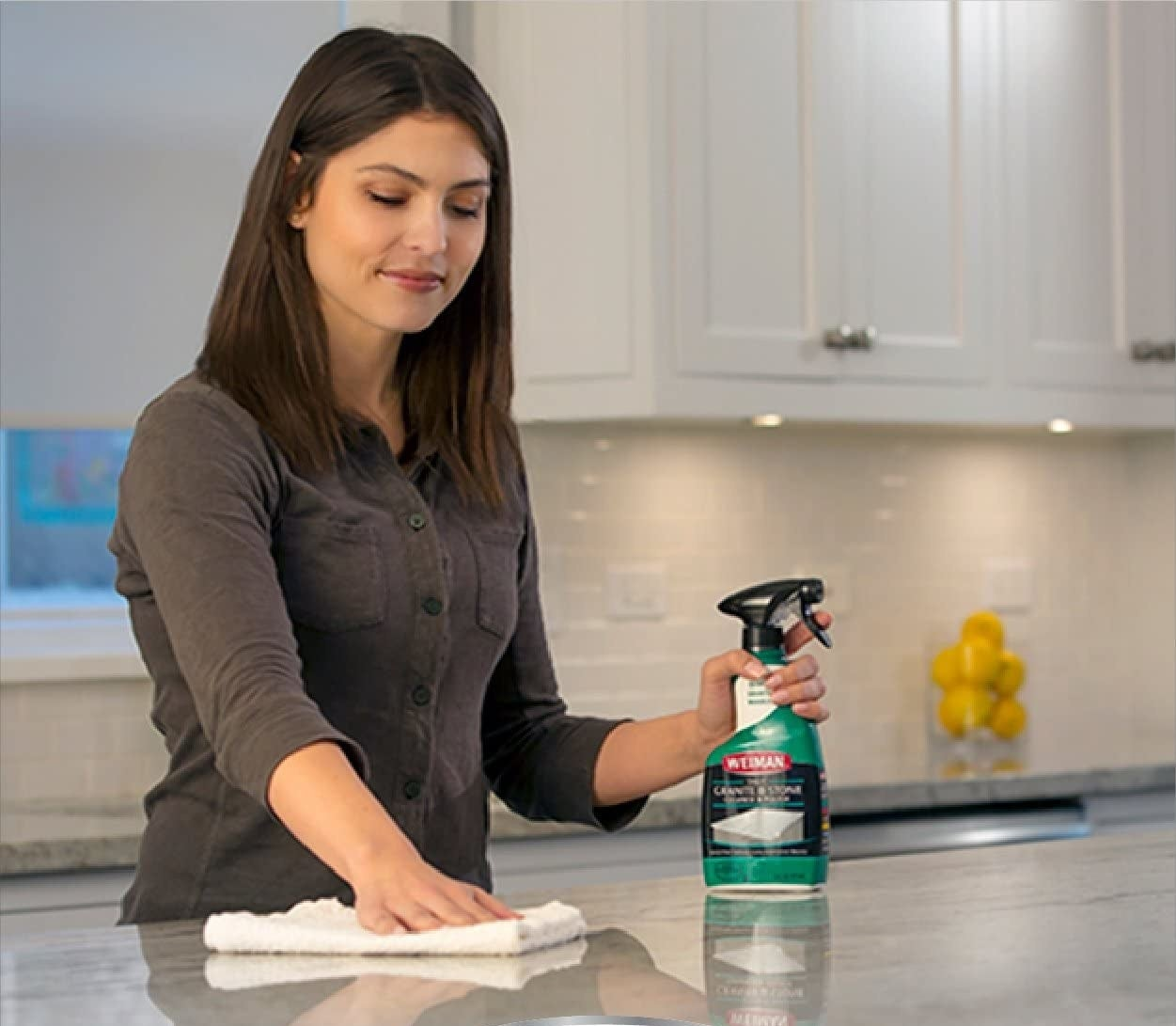 Model wiping counter with cloth and holding bottle of granite cleaning spray