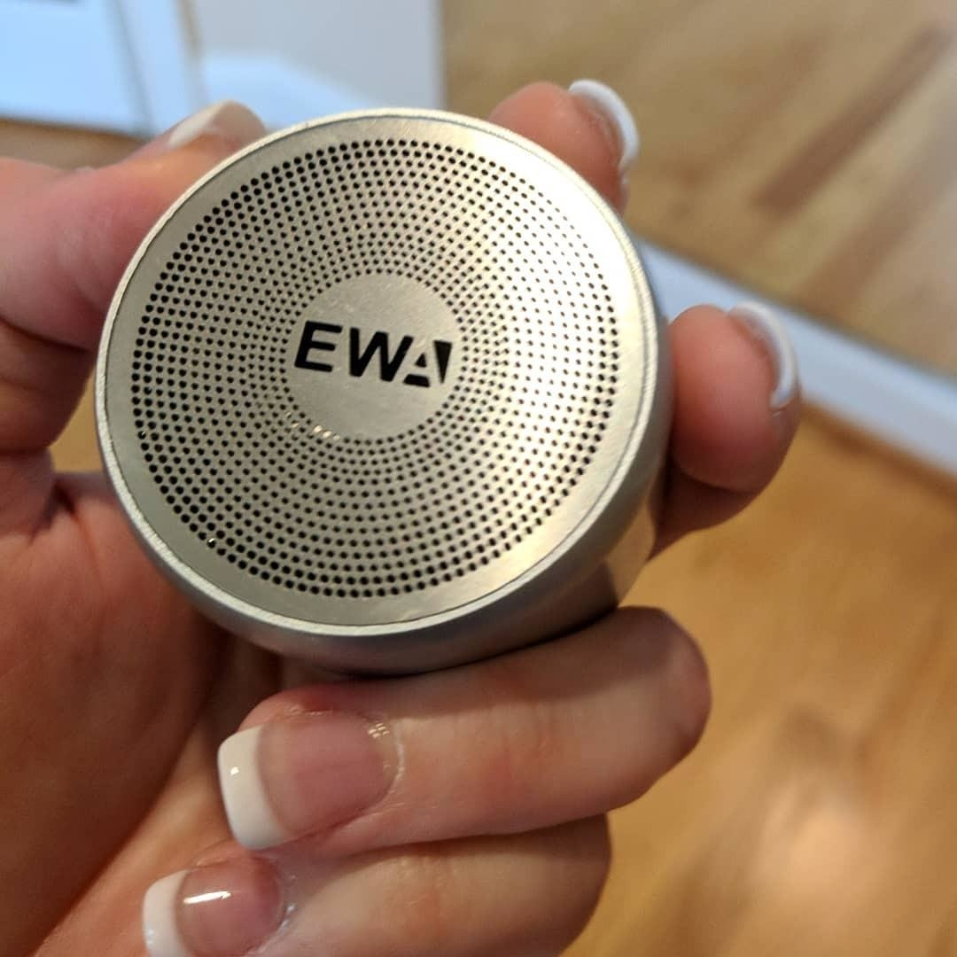 Reviewer holding the palm-size speaker
