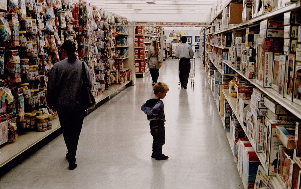 "A photo of a little kid looking at Fisher-Price toys inside a Toys ""R"" Us store."