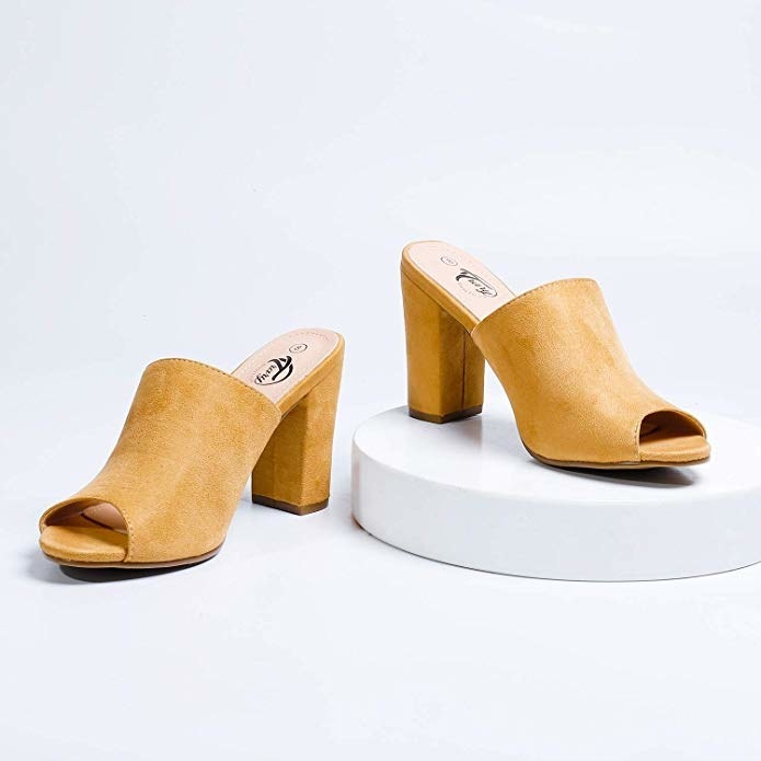 pair of mustard color heeled mules styled on white background