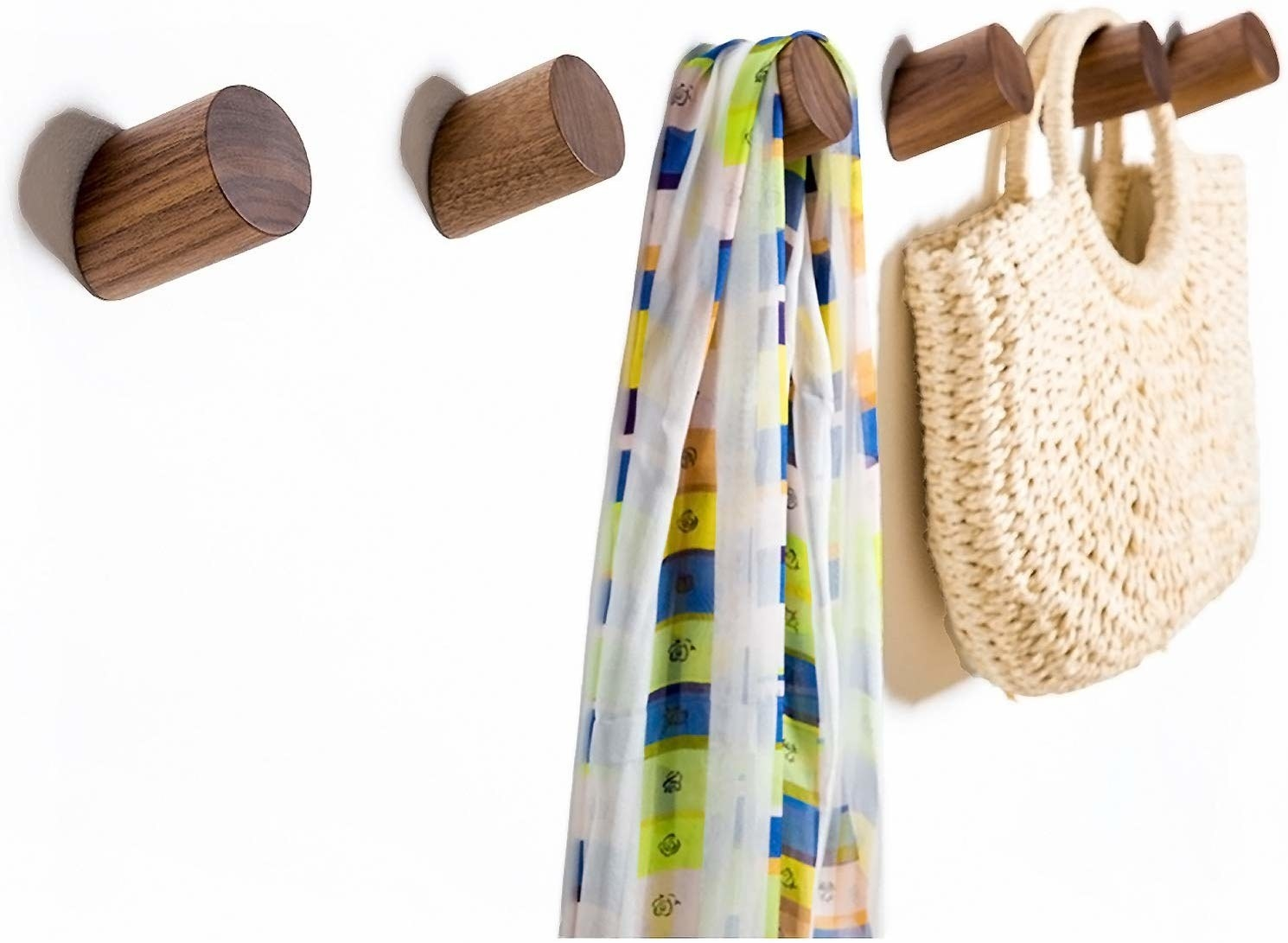 Wooden wall hooks installed to a wall with bags and accessories hanging from them
